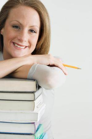 woman with arm resting on stack of books
